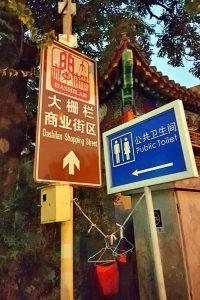 Cartel indicador de baños públicos en Beijing