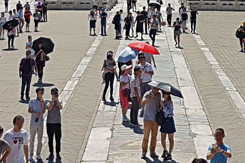 Gente con paraguas visitando la Ciudad Prohibida