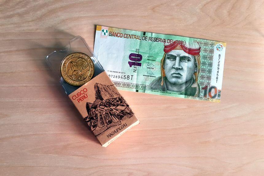 Billete de 10 nuevos soles peruanos y moneda conmemorativa de Machu Picchu